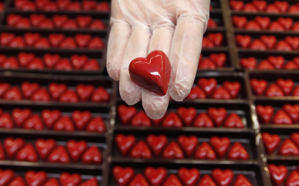 A worker displays a heart-shaped praline for Valentine's Day at a Wittamer chocolate boutique in Brussels February 14, 2012. REUTERS/Francois Lenoir (BELGIUM - Tags: FOOD SOCIETY) - RTR2XTWN